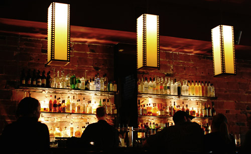 Crime risk factors - A bar or tavern at night with many bottles on the wall behind the counter