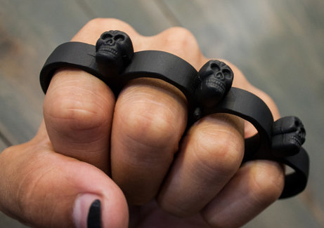Metal knuckles with small skulls on someones fist