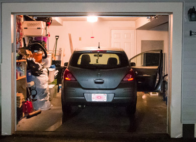 Picture of car parked in a home garage at night