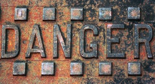 Crime risk factors - Danger sign on metal surface