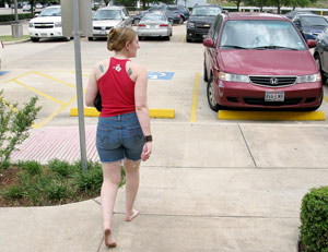 Lady with red top walking to her car in a parking lot