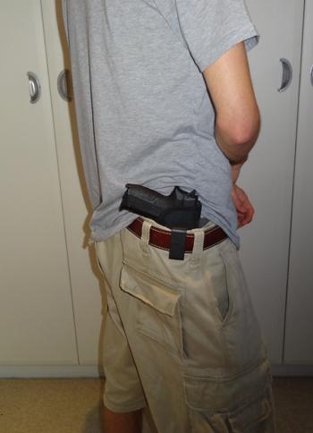 Handgun on belt exposed from under T-shirt