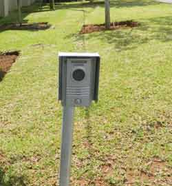 An intercom device on a pole outside the home's gate