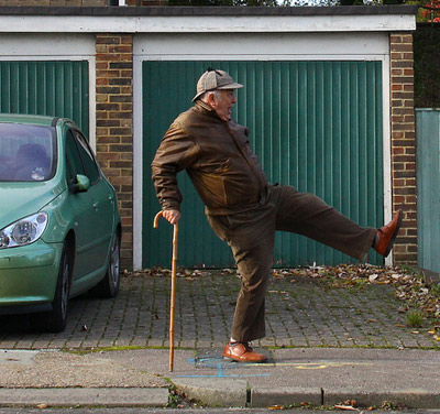 A funny old man dancing in the street with his wooden cane