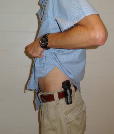 Pepper spray uncovered - lifting up shirt with one hand to expose spray