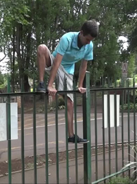 Fence test 2 - Evan climbing over a green steel palisade fence