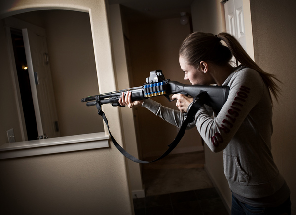 Home defense weapons - Woman pointing shotgun in her home at night