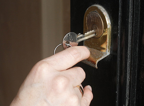 Home Security Door Lock - Someone putting a key into a Yale lock