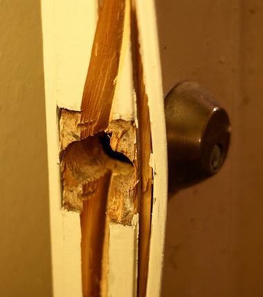 A door thats been kicked in. Split wood is visible.