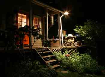 Home security lighting - Dark home with single outside light shining on wooden steps