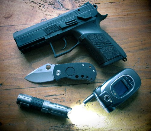 A handgun, knife, flashlight and cellphone on table