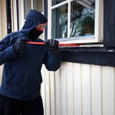 Home Invasions - A masked burglar trying to crowbar a window open