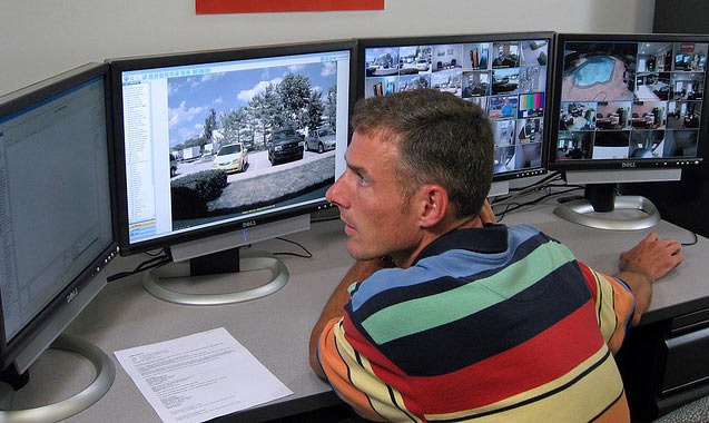Man watching security video camera screens