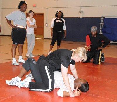 Woman straddling her opponent on the training mat