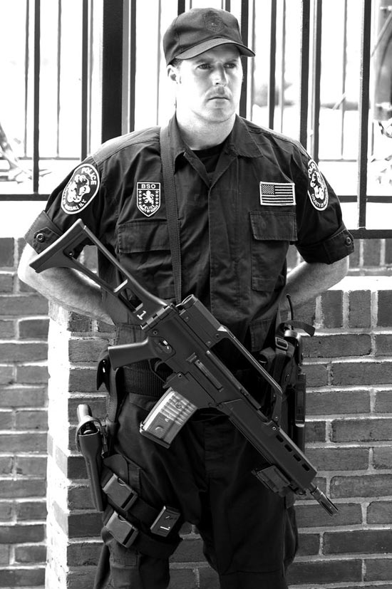 Armed security guard standing with assault rifle across his chest